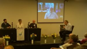 Photo of Sunday afternoon panel discussion participants, from right - Noel Cheer, interviewer; Michael Benedikt via Skype from Texas; Lloyd Geering; Gretta Vosper; Geoff Troughton.