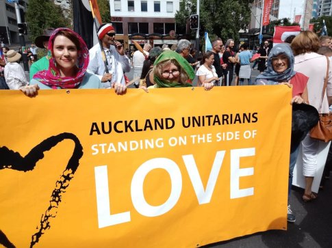 3 church members holding our 'Standing on the side of love' banner, with other marchers in the background